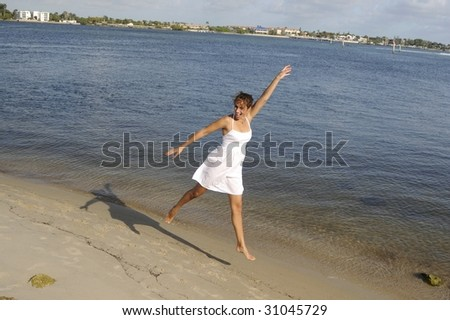 pretty in woman in white dress jumping in the sand at the beach - stock photo