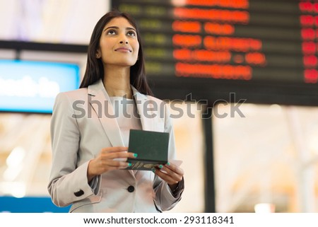 pretty indian business woman checking flight information at airport - stock photo