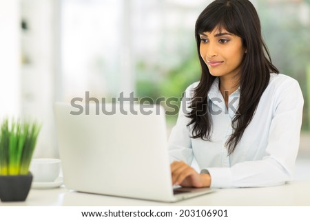 pretty indian businesswoman using computer in office - stock photo