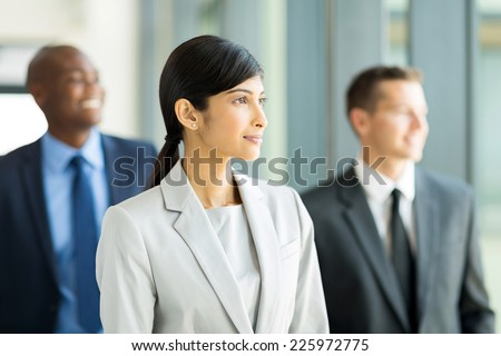 pretty indian businesswoman with group of businesspeople on background - stock photo