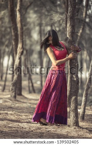 Pretty Indian girl in forrest with traditional dress. - stock photo