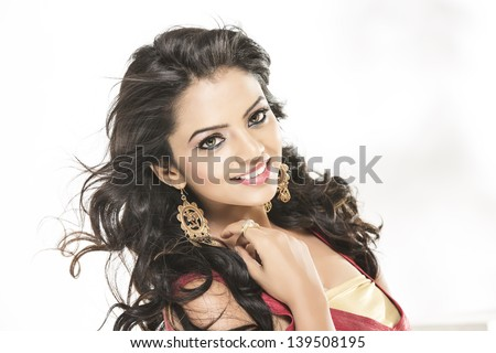 Pretty Indian girl portrait looking at the camera, studio shoot with white background. - stock photo