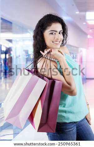 Pretty indian girl smiling at camera while holding shopping bags in the shopping center - stock photo