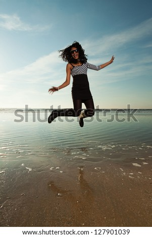 Pretty indian girl with sunglasses on the beach in summer. - stock photo