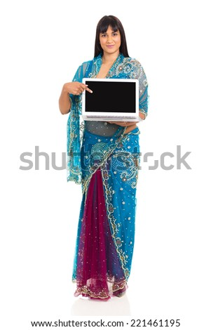 pretty indian woman in sari pointing at laptop screen on white background - stock photo