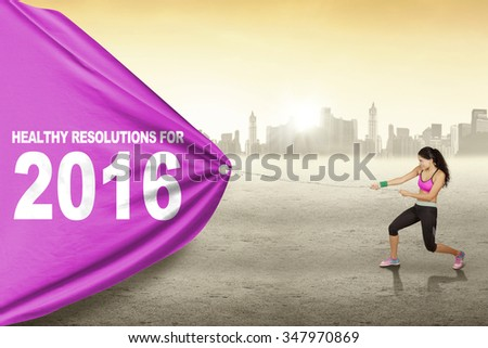Pretty indian woman wearing sportswear and pulls text of healthy resolution for 2016 with a big flag - stock photo