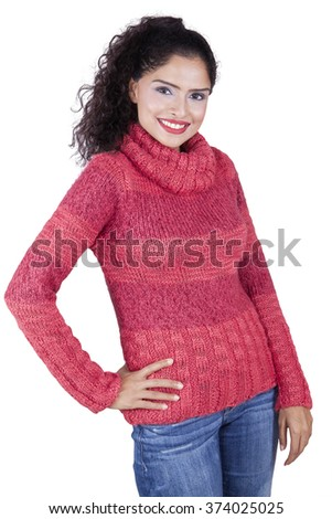 Pretty indian woman wearing winter clothes and smiling at the camera, isolated on white background - stock photo