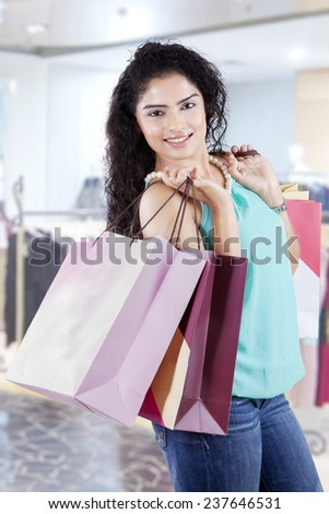 Pretty indian woman with curly hair, smiling at the camera while carrying shopping bags in the shopping center - stock photo