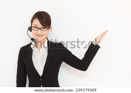 Pretty Japanese business lady in a headset giving a presentation - stock photo