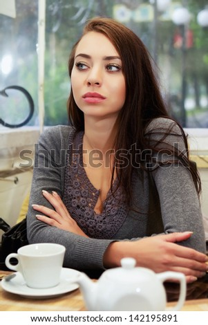 Pretty joyless woman waiting somebody in a cafe  - stock photo