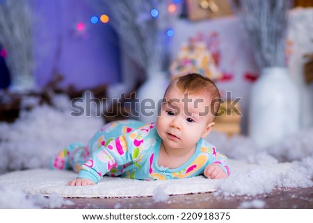 pretty kid girl in a New Year's decor Christmas tree. blue accent decor - stock photo