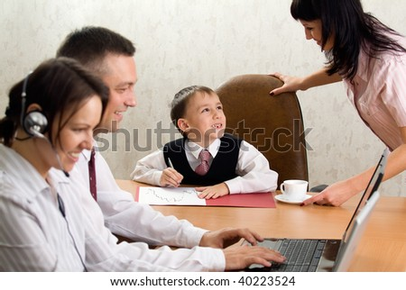 Pretty kid in the office chair with the smiling staff - stock photo
