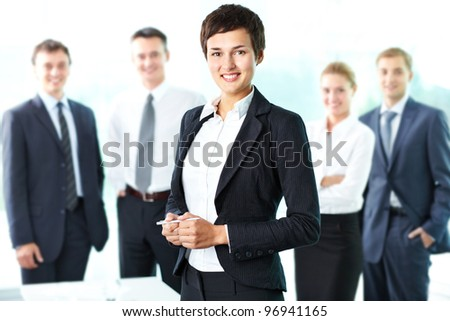 Pretty lady being a successful businesswoman at the head of a strong team - stock photo