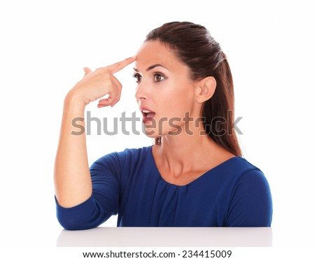 Pretty lady in blue blouse looking to her right while gesturing a headshot in white background - copyspace - stock photo
