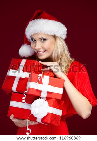 Pretty lady in Christmas cap holds a set of presents wrapped with red paper, isolated on purple - stock photo