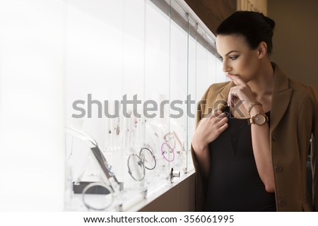 pretty lady , inside a jewellery near a window shop , thinking what to buy , shot in natural ambient light .
