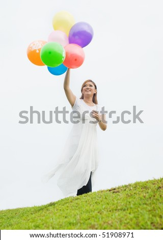 pretty lady with ballon at the hill - stock photo