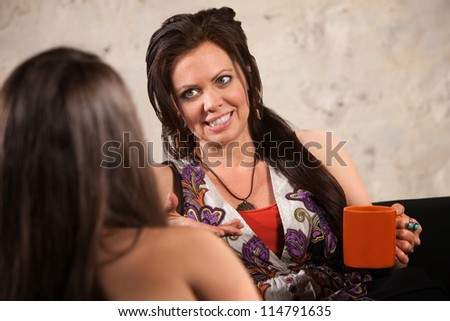 Pretty lady with ceramic cup talking with a friend - stock photo