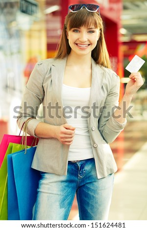 Pretty lady with colorful shopping bags showing credit card - stock photo