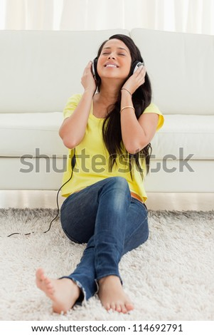 Pretty Latin enjoying music while sitting on the floor - stock photo