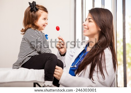 Pretty Latin pediatrician giving a lollipop to a little girl at her office - stock photo