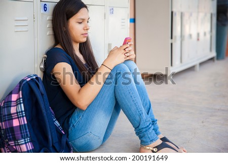 Pretty Latin teen social networking on her smart phone at school - stock photo