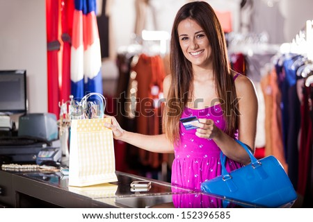 Pretty Latin woman buying some clothes at a store with a credit card - stock photo