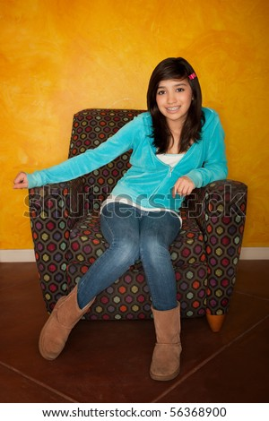 Pretty Latina Girl Seated on Colorful Chair - stock photo