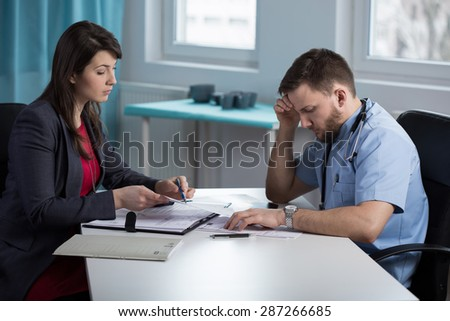 Pretty lawyer and physician talking about doctor's medical error - stock photo