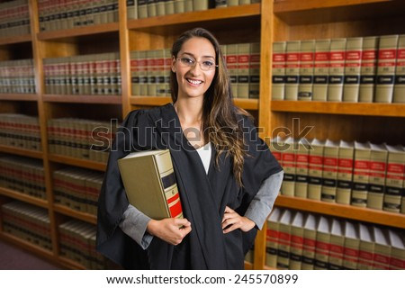 Pretty lawyer looking at camera in the law library at the university - stock photo