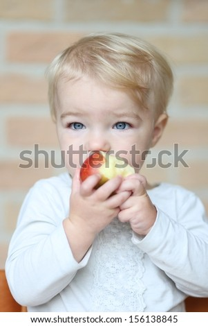 Pretty little blond baby girl bites on tasty red apple - stock photo