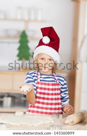 Pretty little blond girl holding out her hand showing off a star shaped Christmas biscuits while baking traditional cookies in Advent - stock photo