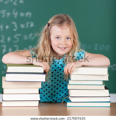 Pretty little blond girl in school with her books smiling happily at the camera while leaning on two high stacks of textbooks - stock photo