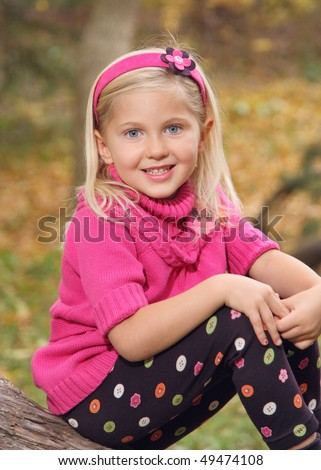 pretty little blond girl sitting outdoors with colorful fall background - stock photo