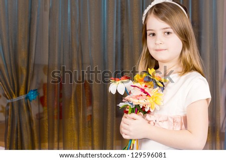Pretty little blonde girl holding a bunch of colouful flowers in her hands against a backdrop of closed curtains with copyspace - stock photo