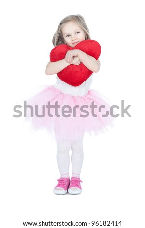 Pretty little blonde girl holding the heart cushion over white - stock photo