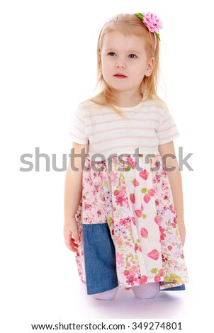 Pretty little blonde girl is kneeling on the floor - Isolated on white background