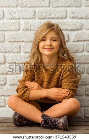 Pretty little blonde girl looking in camera and smiling while sitting cross-legged against white brick wall - stock photo