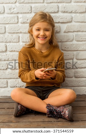 Pretty little blonde girl looking in camera, smiling and using smartphone while sitting cross-legged against white brick wall - stock photo