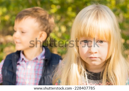 Pretty little blue eyed blond girl staring intently at the camera with a young boy looking to the side in the background - stock photo