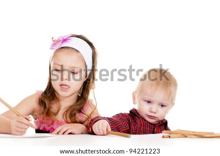 pretty little  boy and girl drawing at table - stock photo