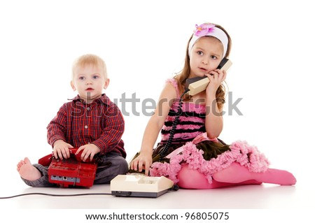 pretty little boy and girl with telephones - stock photo