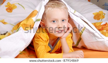 Pretty little boy in bed under the cover - stock photo