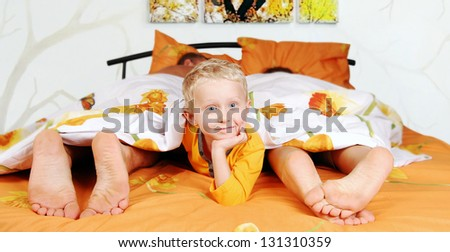 Pretty little boy in his parents bed under cover - stock photo