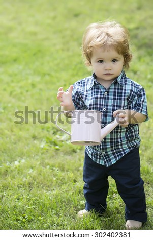 Pretty little boy with blond curly hair in blue checkered shirt and jeans holding white wstering-can looking foward standing on green grass sunny day outdoor copyspace, vertical picture - stock photo