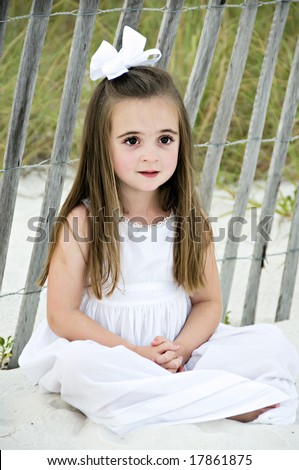 Pretty little brunette girl sitting in the sand wearing a white dress. - stock photo
