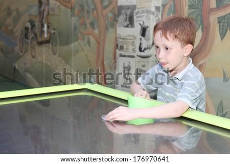 pretty little child playing aero hockey - stock photo