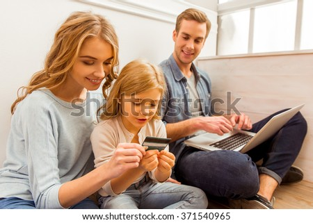Pretty little daughter and her mother holding a creditcard and smiling while sitting near the window at home. In the background beautiful young father using laptop - stock photo