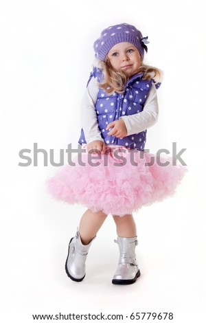 pretty little fashionable girl in pettyskirt and winter vest - stock photo