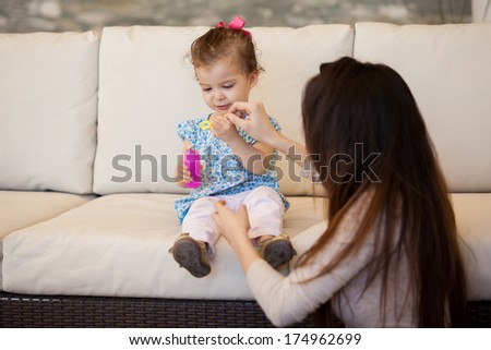 Pretty little girl and her mom blowing some bubbles in the living room - stock photo